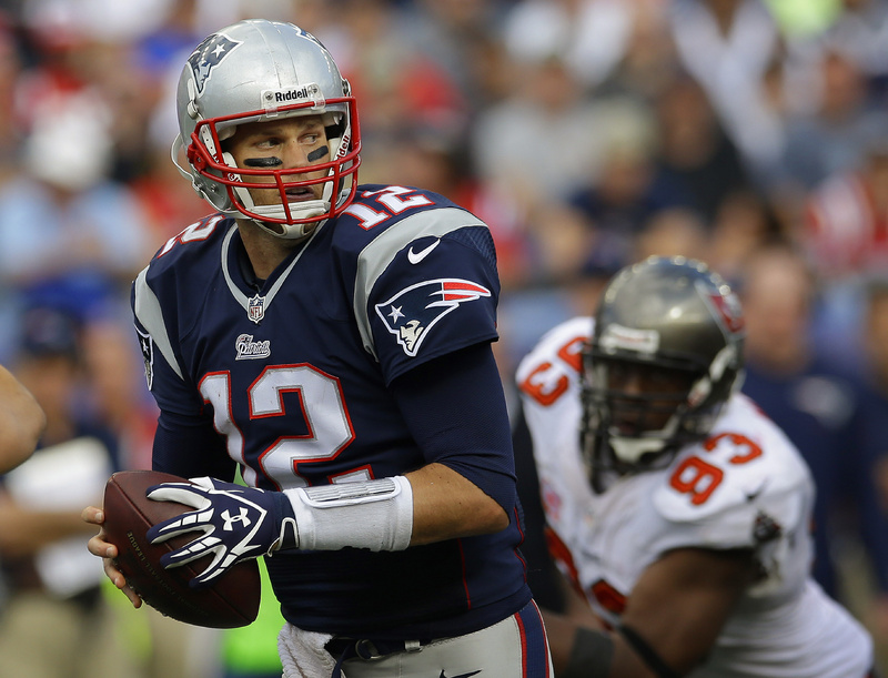 New England Patriots quarterback Tom Brady turns to hand off the ball as Tampa Bay Buccaneers defensive tackle Gerald McCoy moves in during the second half of Sunday's game in Foxborough, Mass.