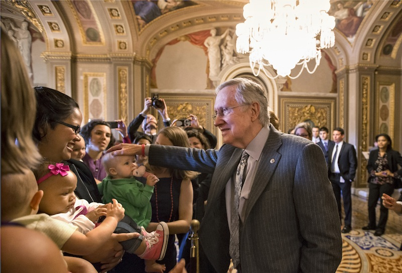 Senate Majority Leader Harry Reid of Nev., and other lawmakers meet with new mothers and their babies on Capitol Hill in Washington, Wednesday, Sept. 25, 2013, to criticize Republican efforts to kill the Affordable Care Act, popularly known as