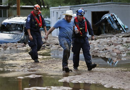 Suffering from dehydration, Lyons, Colo., resident Fred Rob gets help from emergency responders as he leaves his neighborhood after floods left homes and infrastructure in a shambles.