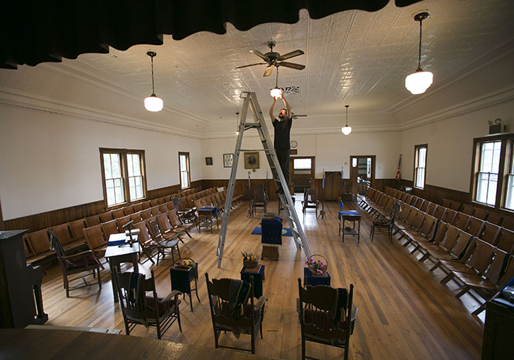 """John Brigance replaces a lightbulb in the meeting room at the West Bath Seaside Grange. Brigance, the grange master, is hoping to recruit new members to keep the 110-year-old grange operating. """"It's a challenge to show people it's still relevant,"""" he says."""
