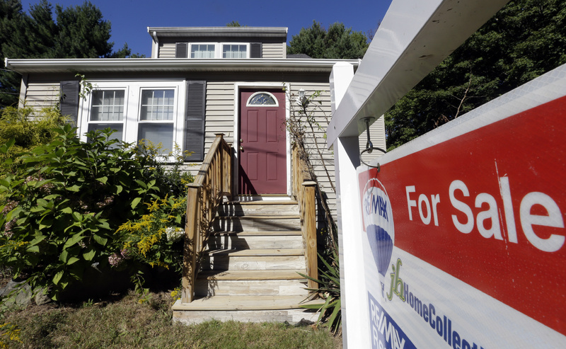 A Re/Max for sale sign hangs in front of a house in Walpole, Mass. Re/Max is among the companies going public next week.