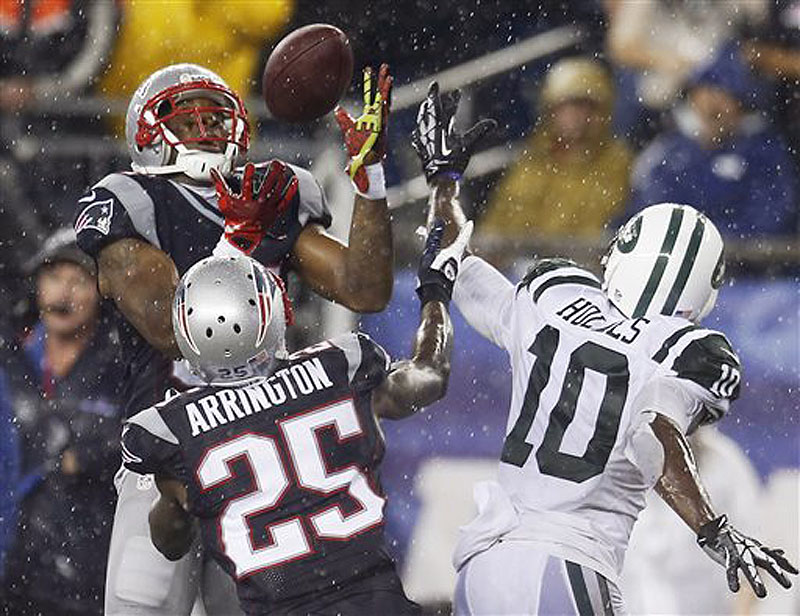 Patriots cornerback Aqib Talib, left, intercepts a pass intended for Jets wide receiver Santonio Holmes (10) in front of Patriots cornerback Kyle Arrington (25) in the fourth quarter Thursday in Foxborough, Mass. NFLACTION13;