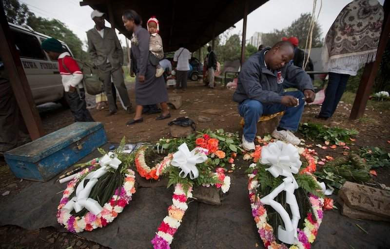 A street-seller makes floral wreaths outside the mortuary in Nairobi, Kenya Wednesday, Sept. 25, 2013. Kenyan authorities prepared for the gruesome task of recovering dozens more victims than initially feared after the country's president declared an end Tuesday to the four-day siege of a Nairobi mall by al-Qaida-linked terrorists. (AP Photo/Ben Curtis)