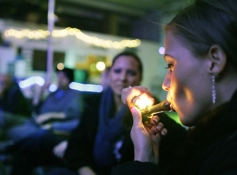 In this in Dec. 31, 2012 file photo, Rachel Schaefer of Denver smokes marijuana on the official opening night of Club 64, a marijuana-specific social club, where a New Year's Eve party was held, in Denver. Bolstered by political victories out West, a marijuana advocacy group is now looking at Maine and other New England states as fertile ground for its next major push to legalize a drug that's gaining wider acceptance from the American public.