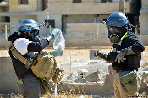 In this Aug. 28, 2013, image provided by the United Media Office of Arbeen, members of the UN investigation team take samples from sand near a part of a missile that is likely to be one of the chemical rockets according to activists, in the Damascus countryside of Ain Terma, Syria.