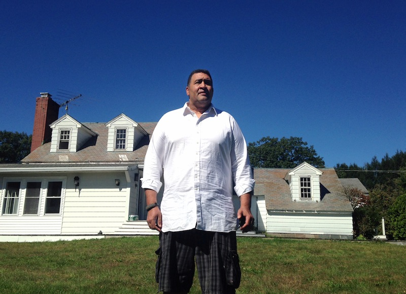 Former NFL offensive lineman Brian Holloway stands in front of his rural vacation home Wednesday, Sept. 18, 2013, in Stephentown, N.Y. Holloway's rural vacation home was trashed during a Labor Day weekend party attended by an estimated 200 to 400 teenagers. Holloway said the partiers caused at least $20,000 in damage, breaking windows and doors, punching holes in walls and spraying graffiti. He saw the whole thing unfold live on Twitter _ and now he's using the teens' own posts to reveal their identities and to try to set them on a better path. (AP Photo/Michael Hill)