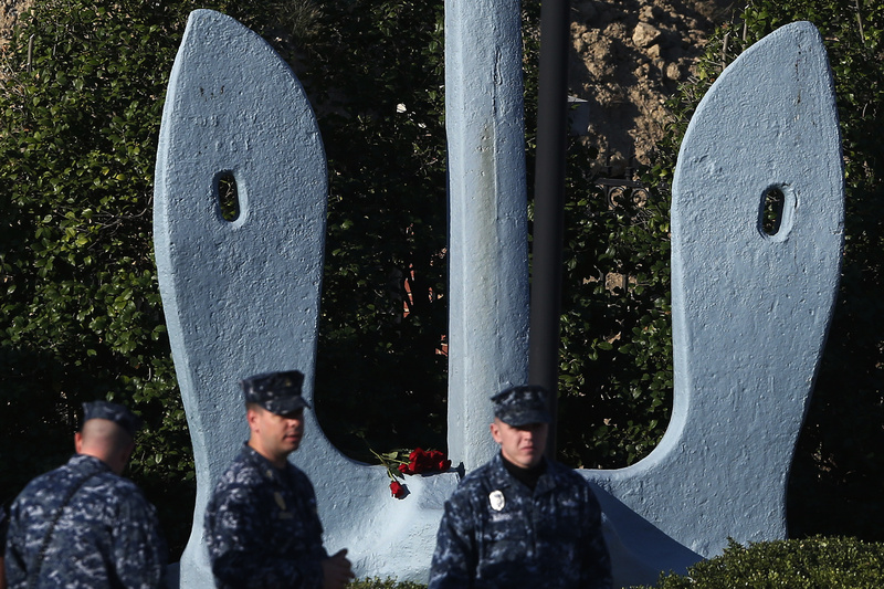Roses that were placed on an anchor at an entrance of the Washington Navy Yard are seen behind security personnel as they stand watch Thursday. The Washington Navy Yard began returning to nearly normal operations three days after it was the scene of a mass shooting in which a gunman killed 12 people.