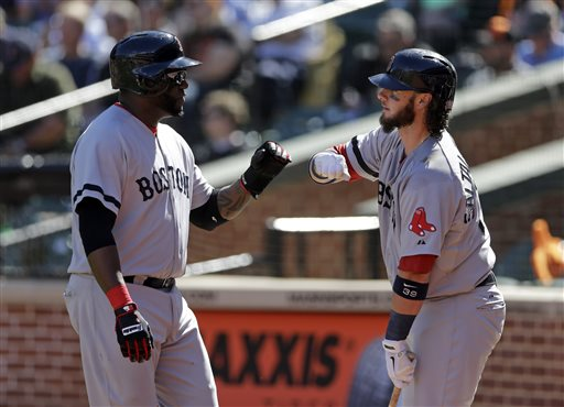 David Ortiz, left, fist-bumps teammate Jarrod Saltalamacchia after scoring a run on a sacrifice ground ball by Mike Carp in the first inning of Sunday's game against the Orioles in Baltimore.