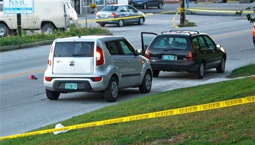 Two vehicles involved in a roadside shooting on North Main Street in St. Albans, Vt., are surrounded by police tape on Wednesday.