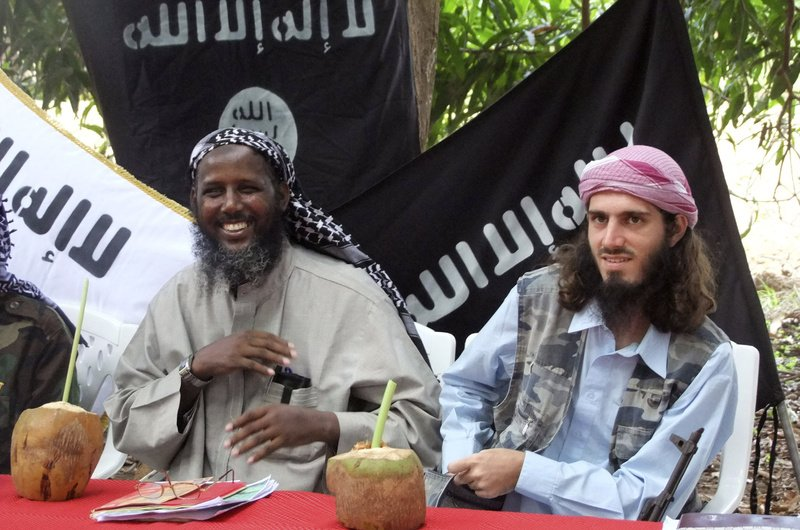 American-born Islamist militant Omar Hammami, right, and deputy leader of al-Shabab Sheik Mukhtar Abu Mansur Robow sit under a banner that reads