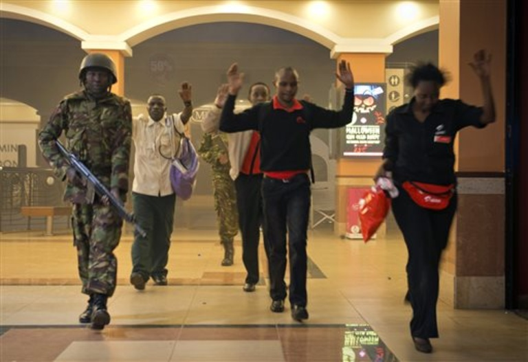 Civilians who had been hiding during a gun battle hold their hands in the air as a precautionary measure before being searched by armed police leading them to safety, inside the Westgate Mall on Saturday.