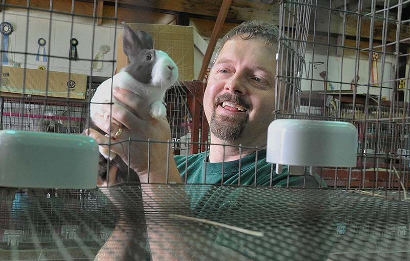 Chris Gurney, representing Archway Rabbitry in Minot, holds one of his Dutch rabbits, recognized as the oldest domesticated breed. Gurney exhibits and sells his rabbits.