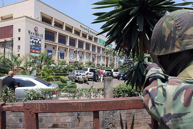 A soldier aims his weapon outside the Westgate Mall, an upscale shopping mall in Nairobi, Kenya on Saturday, where shooting erupted when armed men staged an attack. A witness to the attacks at Nairobi's upscale mall says that gunmen told Muslims to stand up and leave and that non-Muslims would be targeted. Initial police reports had described the incident as a botched robbery. Witnesses say a half dozen grenades also went off along with volleys of gunfire in and around the mall.