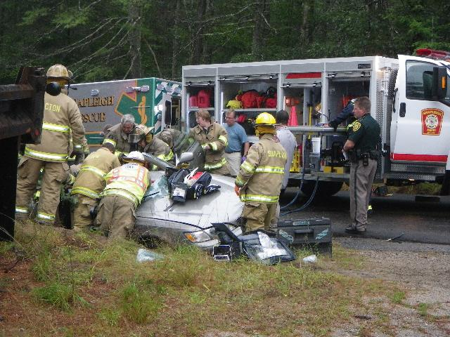 Rescue responders work to extract the occupants of a one-car crash in Shapleigh on Monday, Sept. 2, 2013.