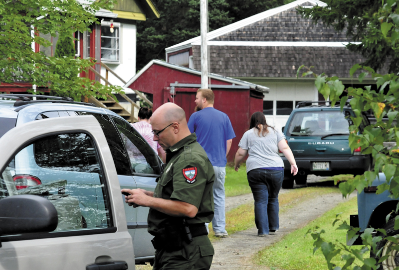 Game Warden Steven Couture prepares to search for Arthur Wakeman, 86, behind his residence in Benton on Thursday, Sept. 12, 2013 as family members arrive at the home. Wakeman was reported missing Wednesday evening.
