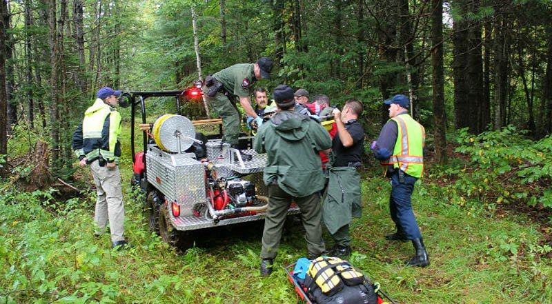 Rescuers takes Arthur Wakeman, 86, out of the woods near his Benton home on Friday.