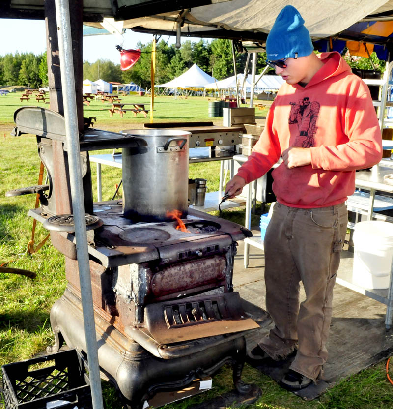 Don Gardner stokes a woodstove with firewood while making yogurt at the Maine Falafel company food booth in preparation for the three-day Common Ground Country Fair in Unity that begins this Friday.
