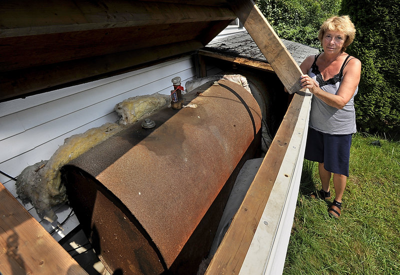 Jo Brillant shows one of the aging oil tanks on her West Bath property that will have to be replaced. The costs of upgrades, combined with an expensive cleanup at another home on her property, climbed to almost $45,000.
