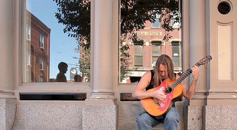 Rick Marr plays a reggae song on his guitar he calls Nikki on Exchange Street in Portland on Aug. 16.