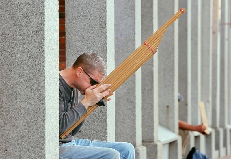 Colin Malakie plays a khaen outside the Thomas Block building on Commercial Street in Portland on Aug. 23.