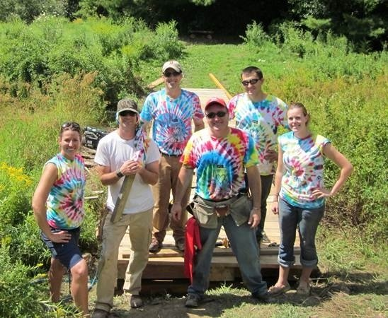 Consigli Construction Co. Inc. Portland office staff volunteers (from left) Alexis Hourigan, Tim Schneider, Dave Thomas, Jim Gardner, Chris Grimaldi and Lindsey Burton pose in colorful tie-dye team T-shirts they made to commemorate their participation in a community volunteer project benefiting the Animal Refuge League of Greater Portland recently. The Consigli team spent the day building a new, wider 40-foot-long bridge to be used by volunteers who walk the shelter's animals through its 72-acre property in Westbrook. The new bridge is now wide enough to allow for trail maintenance equipment to pass through. The lumber for the bridge's reconstruction was donated by Hancock Lumber of Kennebunk.