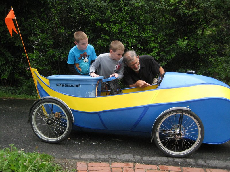 """Jory Squibb of Camden demonstrates his """"hybrid"""" electric quadricycle to Daniel and Ethan Navarro of Rockland. Squibb will be one of the makers exhibiting his """"tinkering results"""" at the Maker Faire on Saturday at the Camden Public Library. His 105-pound Sunbeam car is two-thirds battery-powered and one-third pedal-powered. The range on battery power alone is 80 miles. Midcoast Maine's Mini Maker Faire, the Greatest Show (and Tell) on Earth, is free and open to all ages. It will run from 11 a.m. to 3 p.m. in the library amphitheater."""