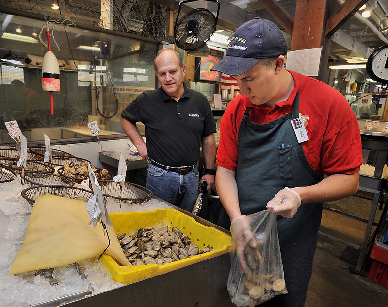 Steve Ponichtera of Gladstone, N.J., watches as retail clerk Luke Parker fills a bag with steamers. Ponichtera said he makes frequent trips to Maine to attend antique auctions and rarely goes home without a selection of seafood from Harbor Fish Market.