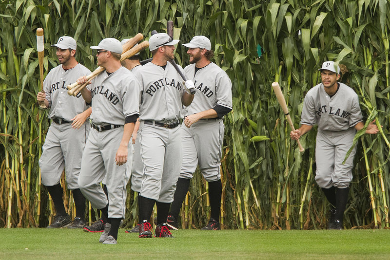 """Dressed in the uniforms of the 1926 Portland Eskimos, the Portland Sea Dogs emerge from the cornstalks in center field during the annual """"Field of Dreams"""" fan appreciation day at Hadlock Field on Sunday. The Trenton Thunder, however, turned on the power in a 9-4 win."""