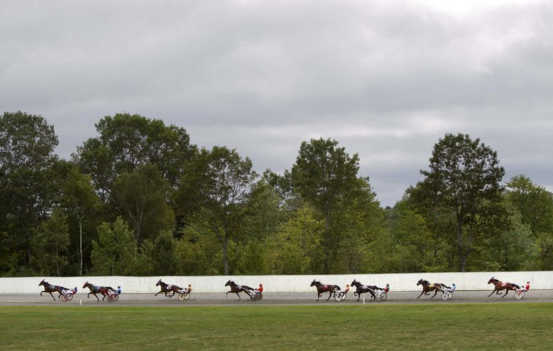 Harness race horses speed down the back stretch Thursday at the Windsor Fair in Windsor. With attendance and betting at racetracks down, and with a drop in casino funding of purses, the industry is uneasy.