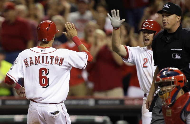 Pinch-runner Billy Hamilton of the Reds gets congratulated by Zack Cozart after scoring the only run Tuesday night in Cincinnati's win over visiting St. Louis.