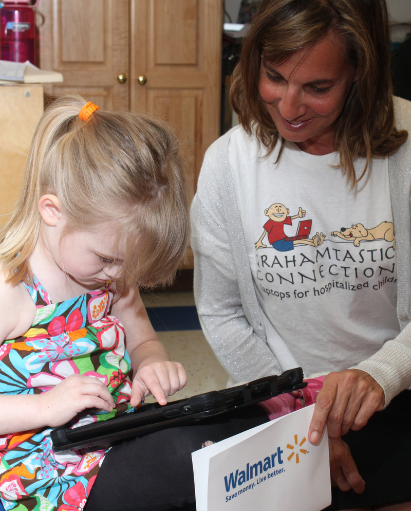 Kilee Graffam, 4, shows Leslie Morissette how she uses one of the iPads donated to Waban by the Grahamtastic Connection.