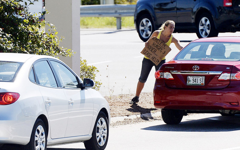 """A woman accepts money from a motorist Friday while panhandling from a median on Route 111 in Biddeford. Her sign reads: """"Homeless, hungry, & sober ... Please help!"""""""