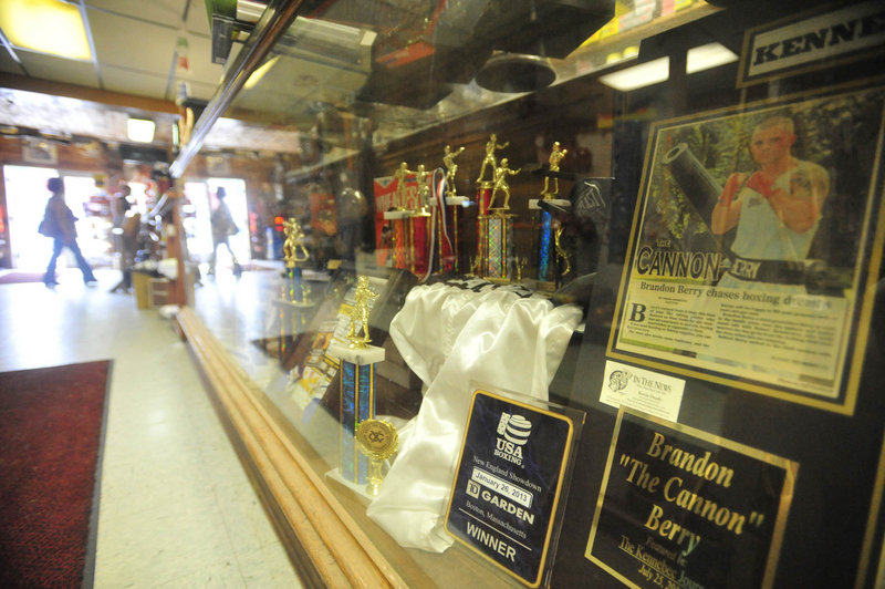 A trophy case highlighting the boxing career of Brandon Berry lines the main aisle in the family's store.