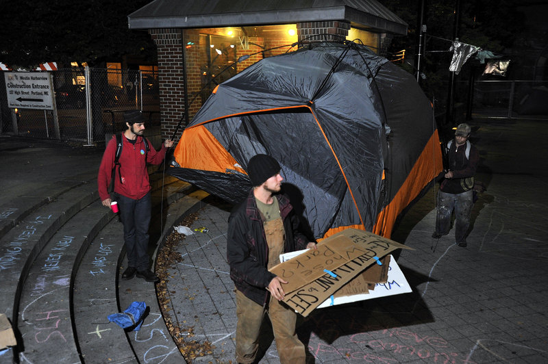 Protesters remove their tent from Congress Square Plaza Friday night after they decided to vacate the area under police orders.