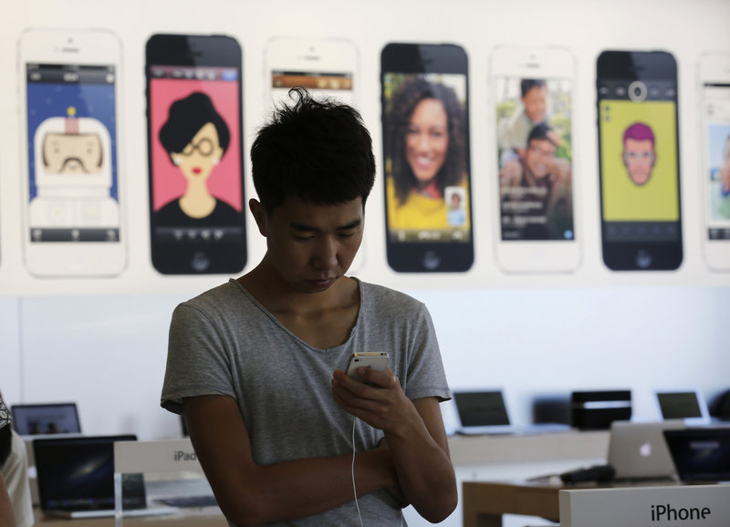 A man tries an iPhone at an Apple showroom in Beijing last week. There is speculation that Apple will unveil a gold version of the iPhone, which could be popular in China, where that color is considered a sign of good fortune.
