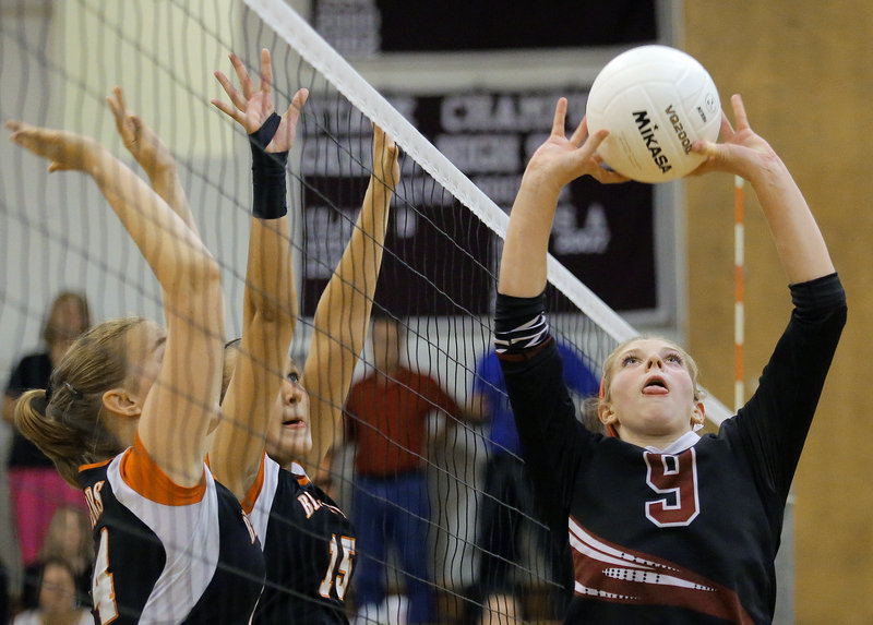 Kaylee Cimino of Greely sets the ball Tuesday night as Phoebe Robinson, left, and Bailey Cote of Biddeford prepare to block during Greely's five-set victory in a high school volleyball match.