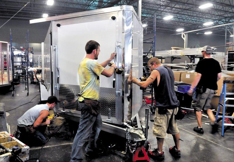 Alcom Inc. employees, from left, Alex Garceau, Jeff Buker and Jason Fecteau, make a snowmobile trailer at the Winslow plant. Alcom employs 185 people in Maine.