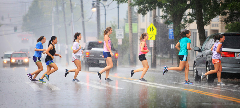 Members of the Portland High School girls' cross-country team dash across Cumberland Avenue Thursday after a drenching training run.