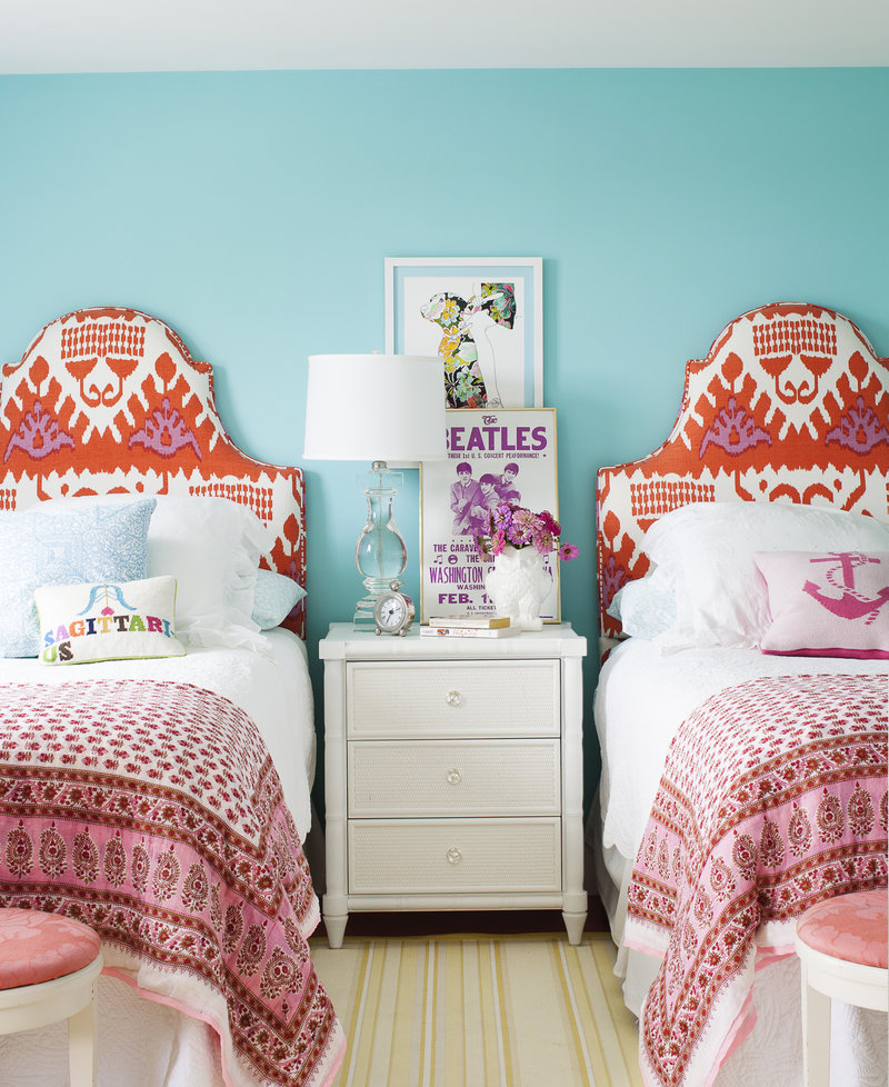 A girl's room, as seen in Country Living magazine, features bright colors and headboards upholstered in a sophisticated ikat print.