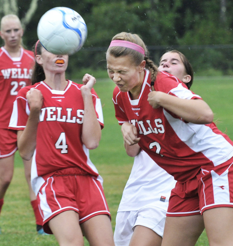 Maddie Taylor of Wells heads the ball in front of teammate Natalie Thurber. The Warriors' comeback bid fell short in a 2-1 loss to Freeport.