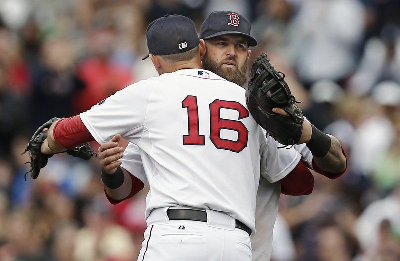 Will Middlebrooks, front, and Mike Napoli celebrate after Boston's 5-1 win over the Yankees on Saturday at Fenway Park. The Red Sox will try for a series sweep Sunday night.