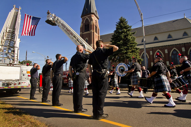 Firefighters salute a color guard leading the way to the Cathedral of the Immaculate Conception in Portland for the annual Blue Mass on Sunday. Hundreds of local, state and federal law enforcement officers, firefighters and other public safety workers were recognized during the Mass for their service.