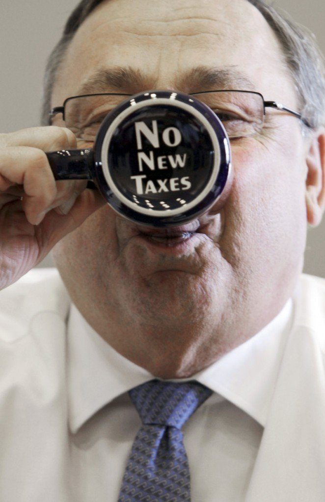 """Gov. LePage takes a sip out of a coffee mug displaying a """"no new taxes"""" message in a 2012 file photo. By declining to accept Affordable Care Act funds to expand MaineCare eligilbility, the governor and his Republican allies in the Legislature saved Maine taxpayers money, a reader says."""