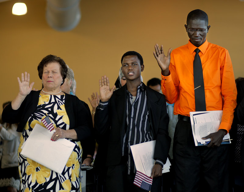 Left to right, Lorisse Matta, 58, of Buxton, originally from Lebanon, Mohamed Ali, 19, of Lewiston, originally from Kenya, and Mamadou Diallo, 32, of Bangor, originally from Mali, were three of 75 immigrants who took the Oath of Allegiance to become U.S. citizens at a Naturalization Ceremony held at Ocean Gateway on Tuesday, Sept. 17, 2013.