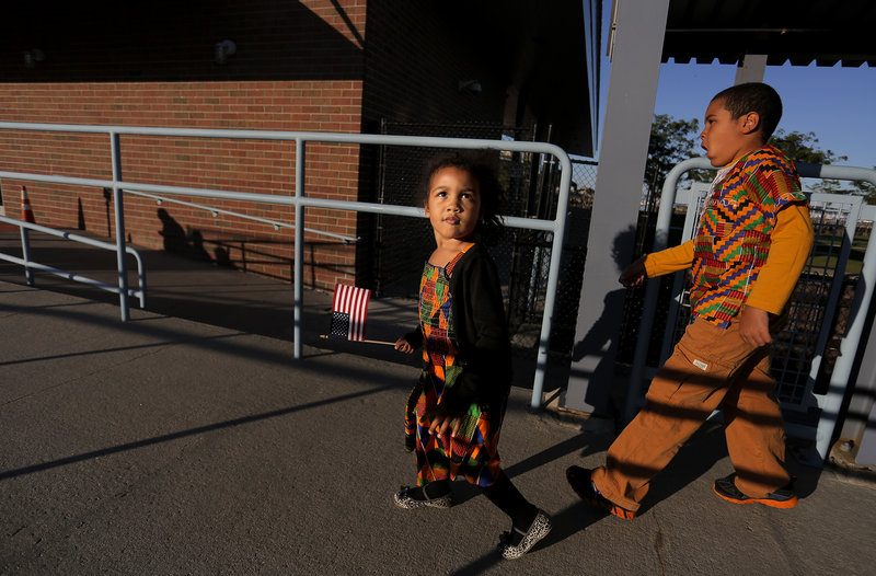 Afia Amoakohene, 3, of Sanford, left, carries an American flag and her brother, Lamar, 7, walks down the ramp at Ocean Gateway after their father Kofi Amoakohene, originally of Ghana, became a U.S. Citizen during a Naturalization Ceremony on Tuesday, September 17, 2013.