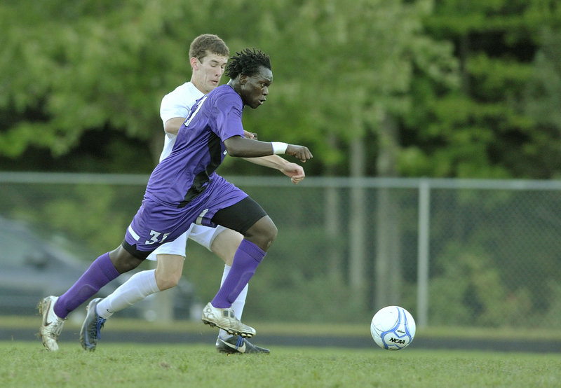 Stephen Ochan of Deering pushes the ball up the field while defended by Morgan Hager-Perry of Gorham. The teams are the top two in the Western Class A Heal point standings.