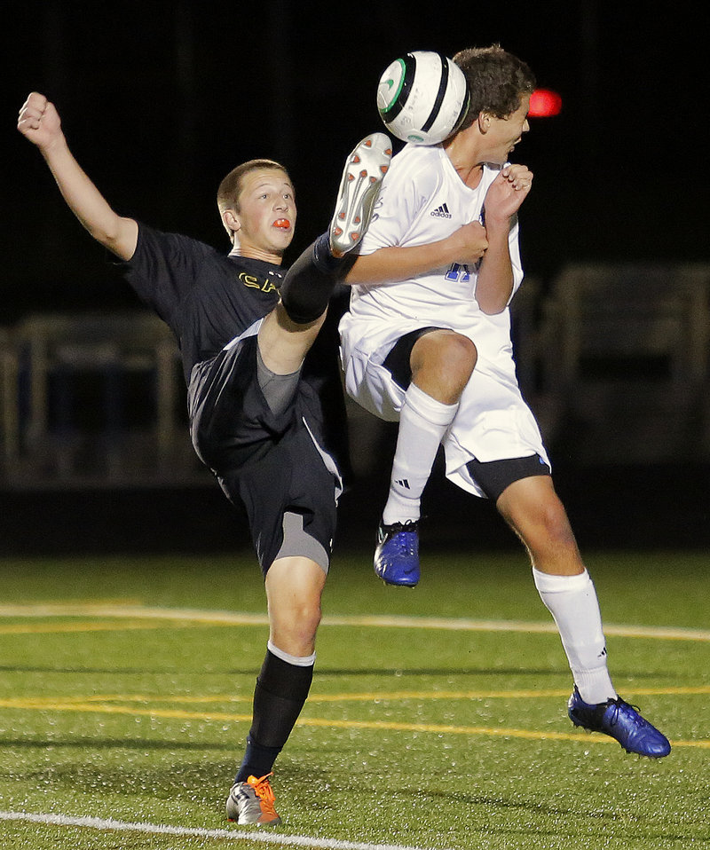 Cole Caswell of Cape Elizabeth, left, goes a bit high for the ball as Falmouth's Jonah Spiegel awaits the contact during the first half of a scoreless tie Wednesday night in Falmouth.