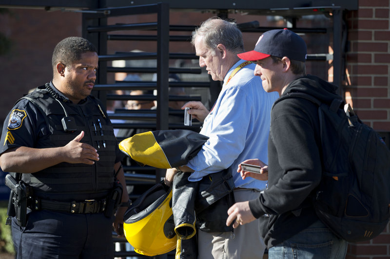 A police officer answers questions as employees ready their identification at the Navy Yard in Washington on Wednesday.