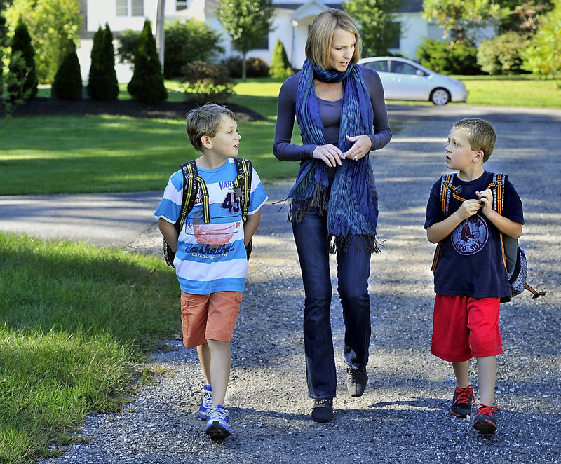 Moss walks from the school bus with her sons, Quinn and Rowen Hagerty. Having more time with them has been a benefit of leaving her TV station job.