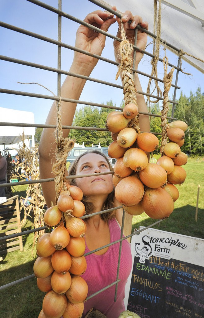 Emily Goodchild, from Stonecipher Farm in Bowdoinham, hangs strings of onions on their stall at the Common Ground Fair on Friday.
